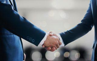 Shady businessmen shaking hands